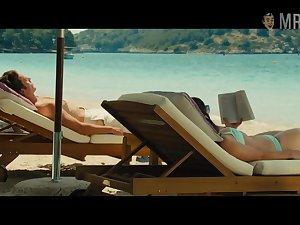 Emilia Clarke in swim suit is sunbathing by the poolside